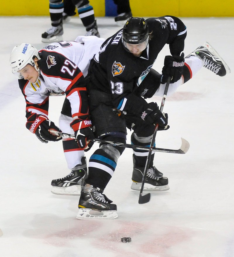 Igor Gongalsky of the Portland Pirates, left, attempts to take the puck from Matt Pelech of the Worcester Sharks. The Pirates won in OT.
