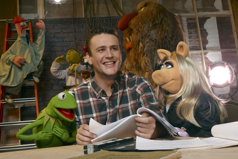 Jason Segel with muppet characters Kermit the Frog and Miss Piggy, in a scene from