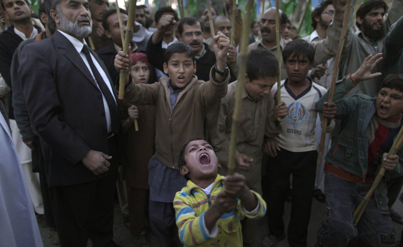 A Pakistani boy, front, shouts slogans along with other protesters during a rally on the outskirts of Islamabad on Sunday to condemn a NATO attack that killed 24 Pakistani troops. The fallen soldiers' funerals were broadcast on television.