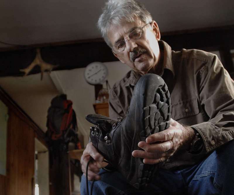 Nelson Daigle talks about the boots he has worn out over the years at his Millinocket home. Daigle has hiked Maine's tallest mountain more than 400 times over the past 17 years.
