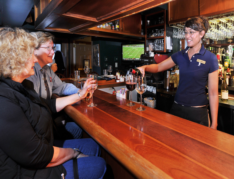 Barb Palmer, left, and Gayle Mooney, both from South Dakota and in Maine visiting relatives, watch as bartender Michelle Alexander pours a glass of wine at the Broad Arrow Tavern, located inside the Harraseeket Inn in Freeport.