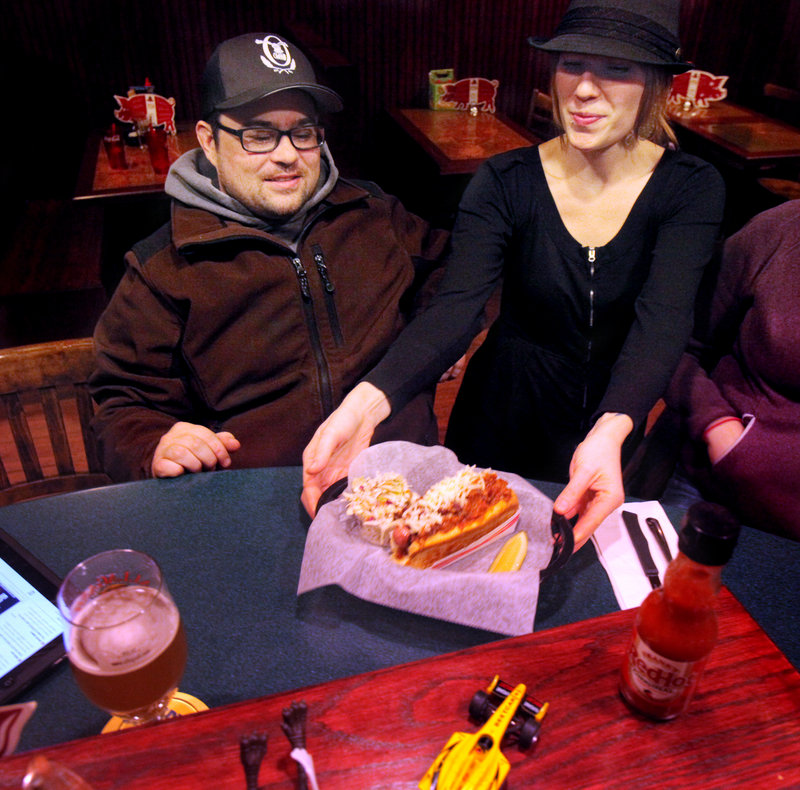 Kate Pierce, right, serves a Sausage Chili Bomb to Tony Ries at The Thirsty Pig in Portland.