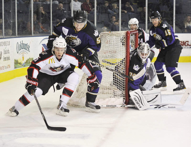 Marc-Antoine Pouliot of the Portland Pirates carries the puck around the net while being pursued by Jordan Hill of the Manchester Monarchs.