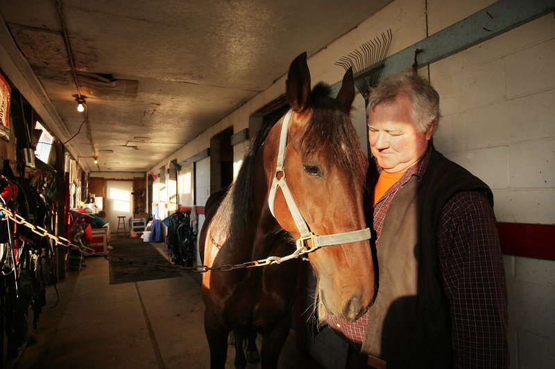 Ernie Lowell talks to Best Edition on Friday in a stable at Scarborough Downs, where he has been shoeing horses for 43 years. Lowell has been worried about the future of the track and the harness racing industry in general since a proposed racino in Biddeford was defeated last month.