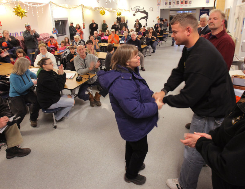 Kathleen MacKenzie, Jackman's town manager, shakes hands with Sgt. Timothy Gilboe at a reception after a parade honoring Gilboe in Jackman on Thursday.