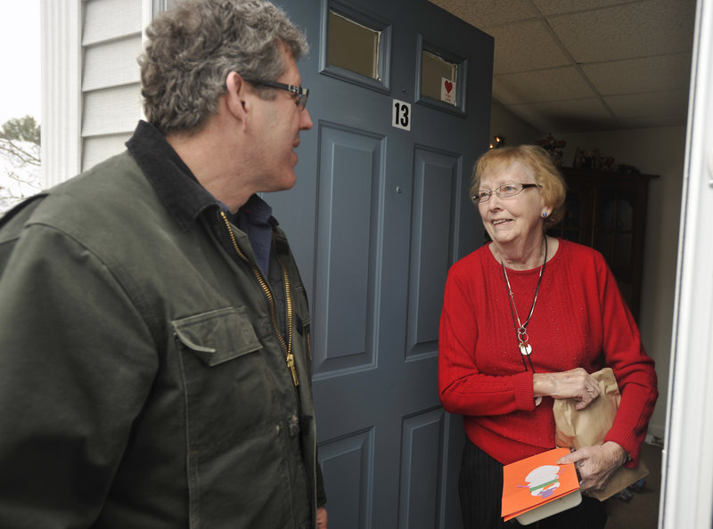Volunteer Greg Shinberg chats with Meals on Wheels client Kathy Porier at her Westbrook home after making a meal delivery on Christmas Day.