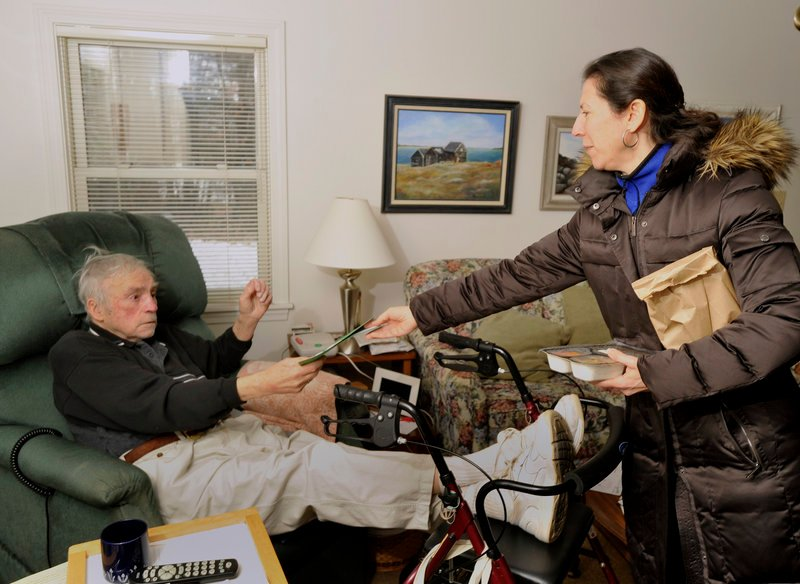 Leah Cantor hands client Ken Luce, 91, a Christmas card made by a Westbrook student after dropping off a ham dinner Sunday at his Westbrook home.