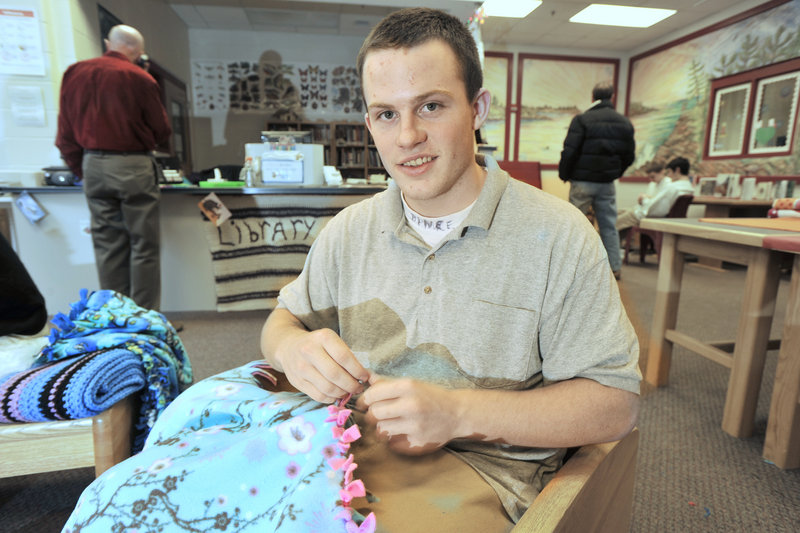 """D.J. Cressey, 17, of Brunswick ties the tabs on a blanket. He says the work is rewarding because """"I'm giving this to someone else! For once I'm giving back everything I've taken."""""""