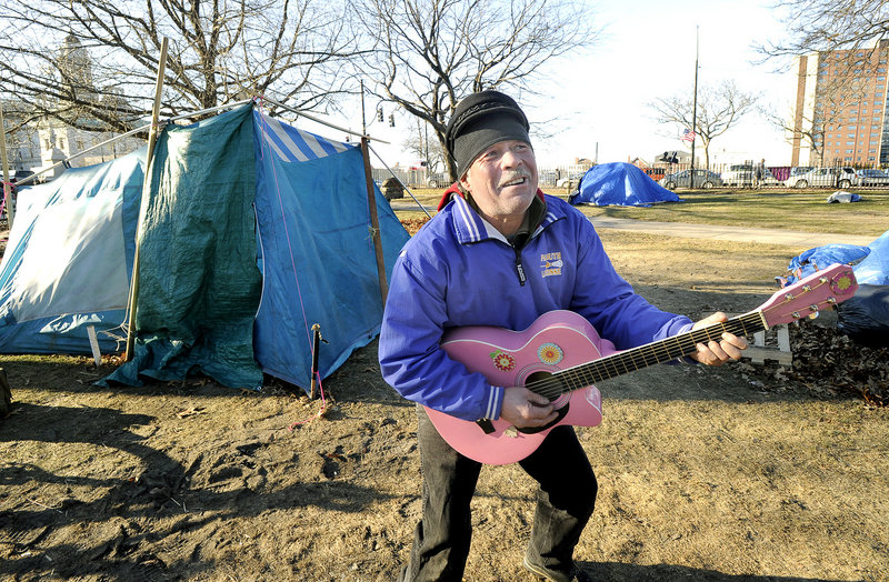 "Bobby Davis, 51, plays his pink guitar Thursday at the park. ""It's tough to survive,"" the Falmouth man said."