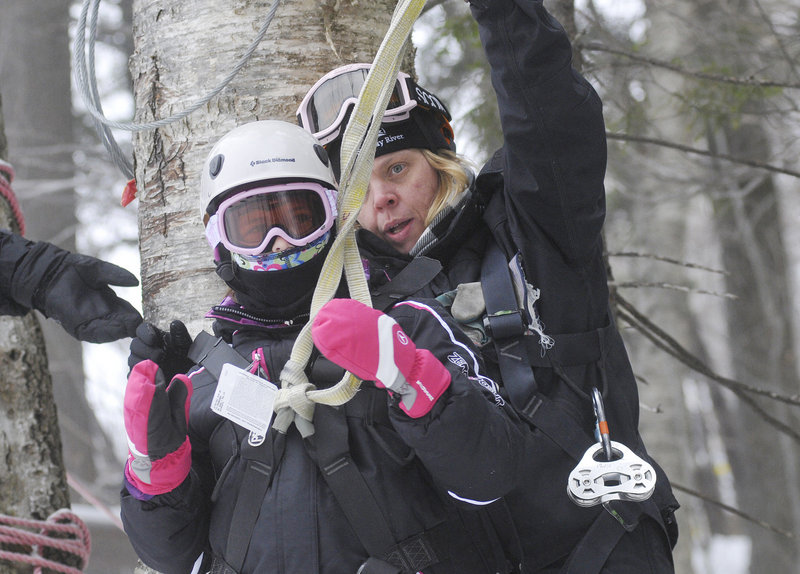 Hannah Connell, 10, of Orlando, Fla., gets hooked up to her zip line with the help of guide Patty Pittman at Sunday River in Newry on Friday.