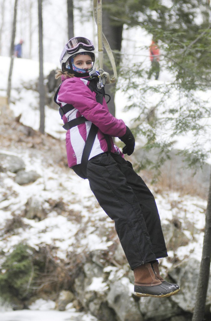 Lauren Connell, 12, of Orlando, Fla., moves down a zip line at Sunday River in Newry on Friday, while staying tightly bundled in her winter gear.