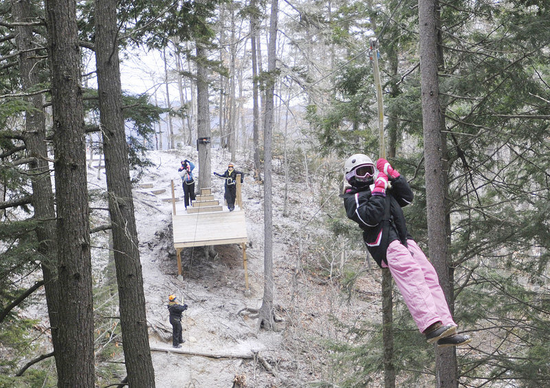 Hannah Connell, 10, of Orlando, Fla., a moves through the forest on a zip line at Sunday River in Newry on Friday.