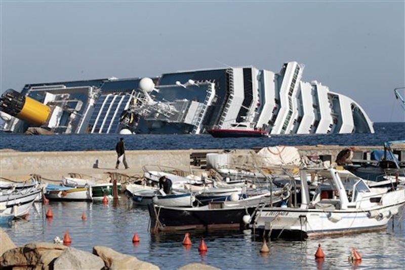 The luxury cruise ship Costa Concordia leans on its starboard side as seen from the Giglio harbor. The luxury cruise ship ran aground off the coast of Tuscany, sending water pouring in through a 160-foot (50-meter) gash in the hull and forcing the evacuation of some 4,200 people from the listing vessel early Saturday. (AP Photo/Gregorio Borgia)