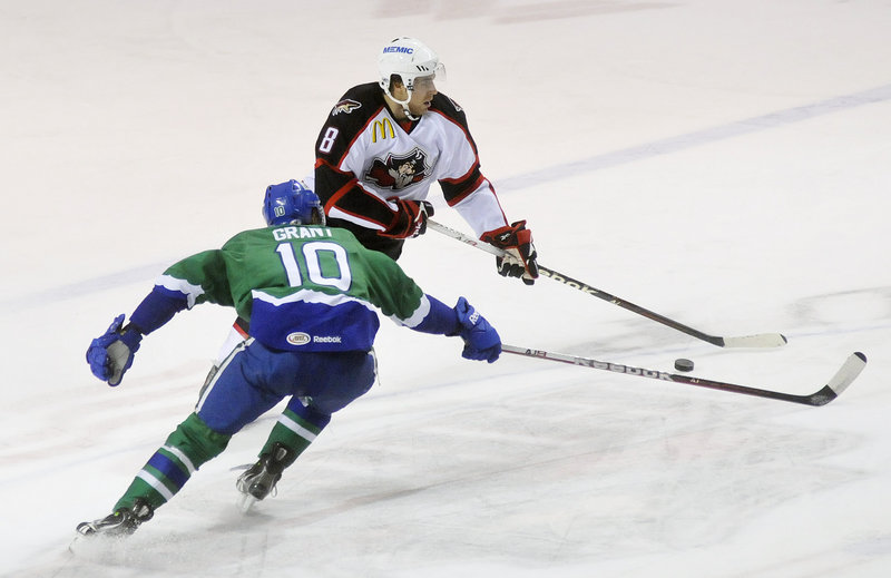 Ethan Werek of the Pirates tries to elude Connecticut's Tommy Grant in Monday's game at the Cumberland County Civic Center. The Pirates wiped out a three-goal deficit to pull out a win in overtime.