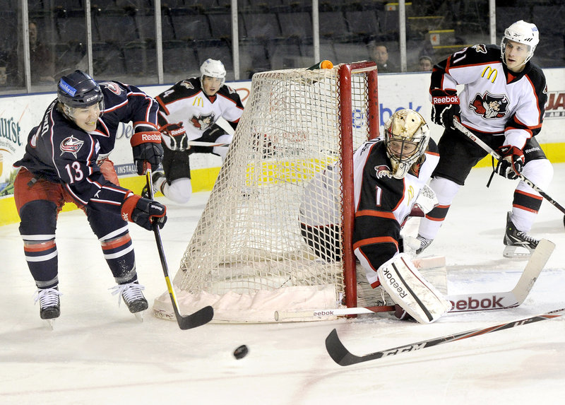 Cam Atkinson of the Falcons makes a pass as Pirates goalie Justin Pogge watches the puck Friday night. Atkinson scored his 22nd goal of the season, but Portland earned a 5-3 win.