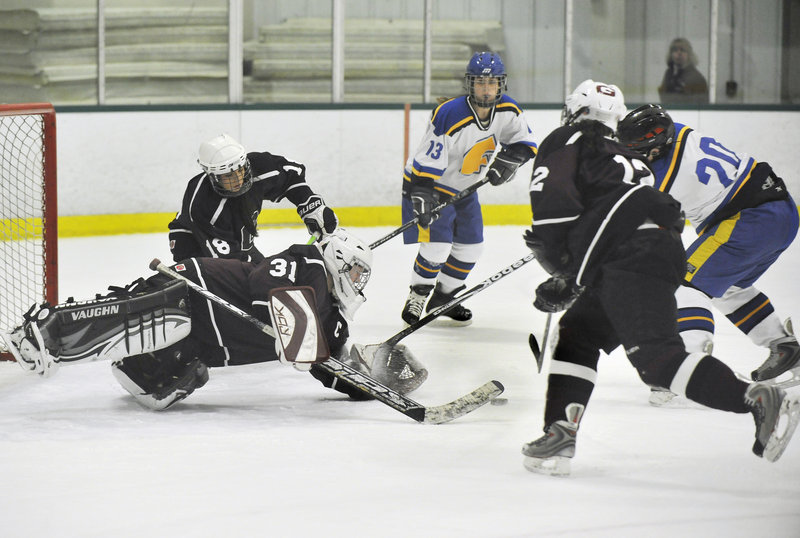 Greely goalie Emma Seymour dives to cover a loose puck as Falmouth's Maddy McDonnell moves in on the play Monday night at Family Ice Center in Falmouth. Falmouth earned the win with three third-period goals.