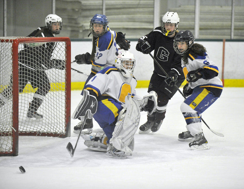 Falmouth goalie Kirsten Mazur kicks away a scoring bid from Greely in Monday night's girls' hockey game at Family Ice Center in Falmouth. Mazur made 29 saves as the Yachtsmen pulled away for a 4-1 victory to finish the season 17-1.