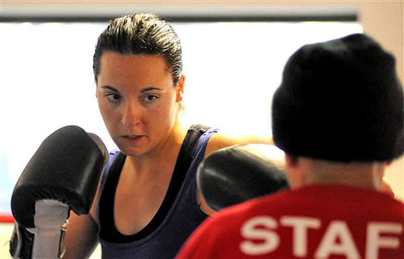 In this Feb. 15, 2012 photo, Ellyn Guinding, 31, of Worcester, Mass. trains with assistant coach Carmelo Torres at the Boys & Girls Club in Worcester. Ellyn will face her fraternal twin sister, Kerri Lewis, in the boxing ring for what promises to be a no-holds-barred slugfest on May 3 at the Worcester Palladium. (AP Photo/Worcester Telegram & Gazette, John Ferrarone)