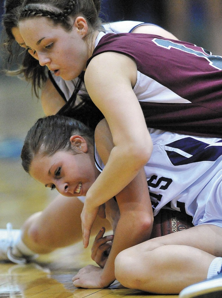 Kylie Richards, top, of Nokomis battles for a loose ball with Presque Isle's Chelsea Nickerson in the Eastern Class B championship game at the Bangor Auditorium. Nokomis, which was aiming for its third straight regional title, lost 52-40.
