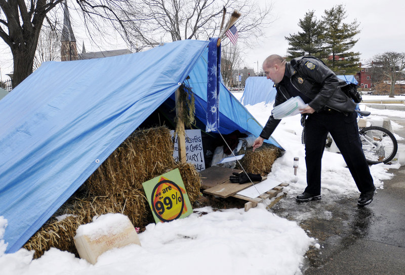 Sgt. Andy Hutchings drops off a notice to vacate at a tent in Lincoln Park in Portland on Thursday. The city is giving Occupy Maine protesters until Monday morning to move out.