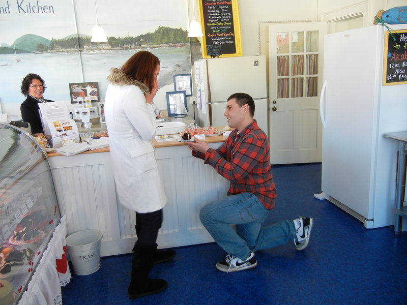 The would-be groom proposes to his beloved at Cranberry Island Kitchen in Portland, with the ring concealed in a whoopie pie and store co-owner Karen Haase looking on approvingly. Michael and Amber Snyder were married on Jan. 10.