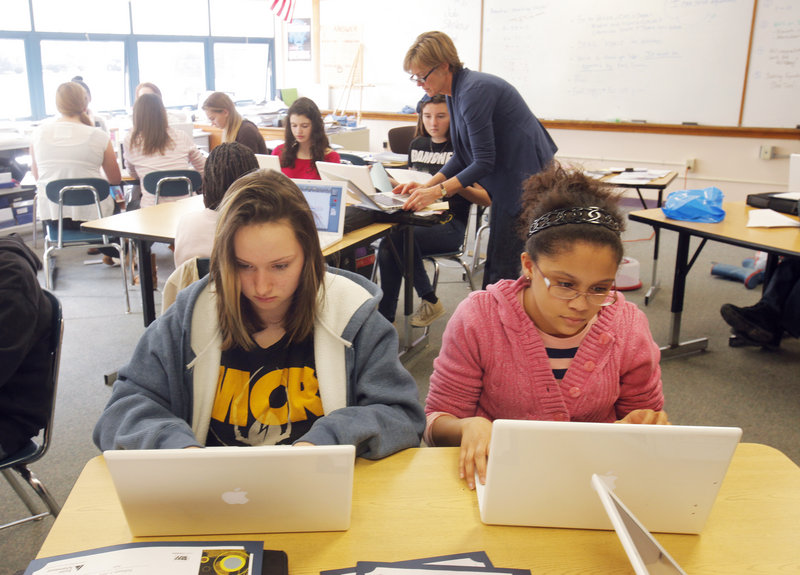 Jessy Brewer, left, and Kiara Neal work on their laptops in Ann Young's math class at King Middle School. Portland expects to receive 6 percent more state school aid in 2013.