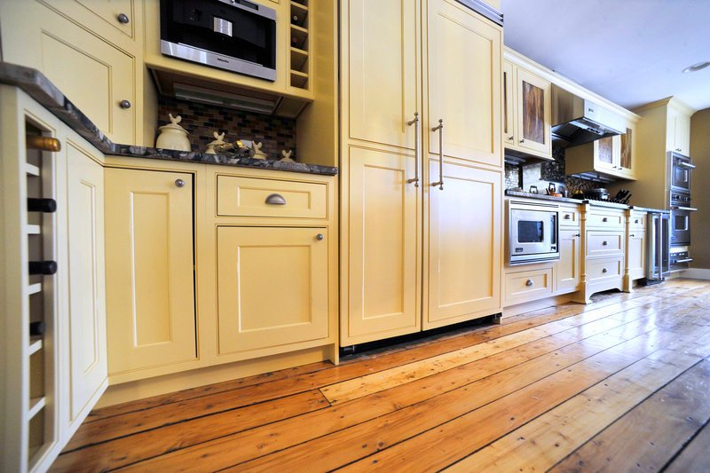 The original pumpkin pine floors of the old barn were refinished to their natural beauty. The kitchen blends farmhouse style with modern convenience.