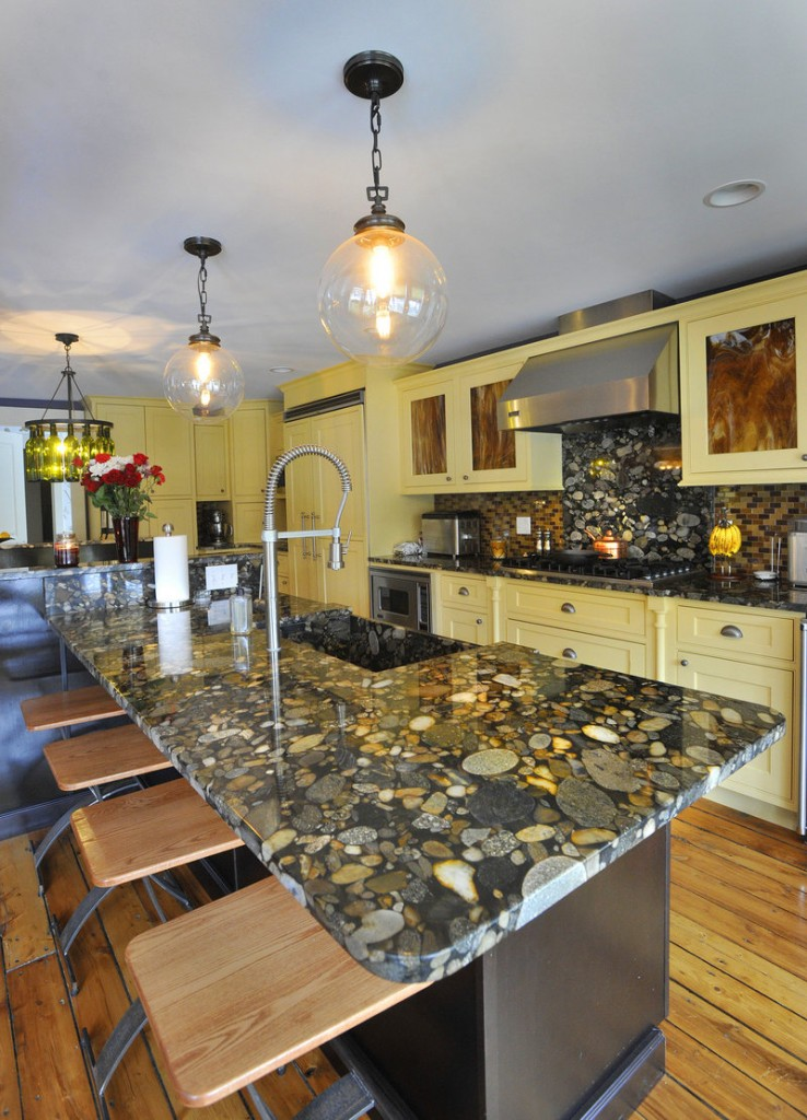 Stunning marinace granite tops the kitchen island and counters, and resembles river rock under water.