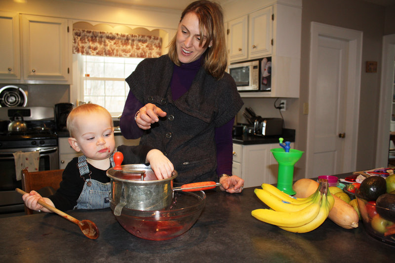 Christine Wirth and her 14-month-old son, Joseph, make applesauce using a metal food mill.