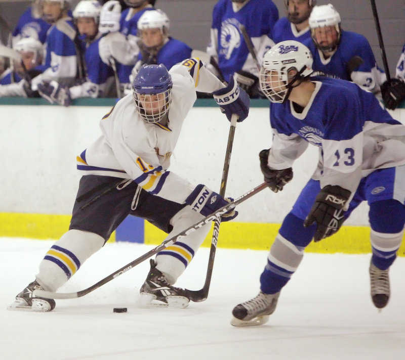 Ben Freeman, left, who scored five goals for Falmouth, attempts to skate around Nick Manuel of Kennebunk.