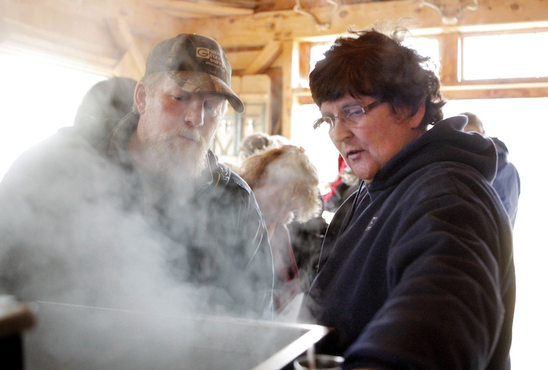 At her sugar house in Gorham, Jo Hartwell explains the sugaring process to Scott Sorenson, also of Gorham, during Maine Maple Sunday on Sunday, March 25, 2012. Sugar houses throughout Maine opened their doors to visitors on Sunday.