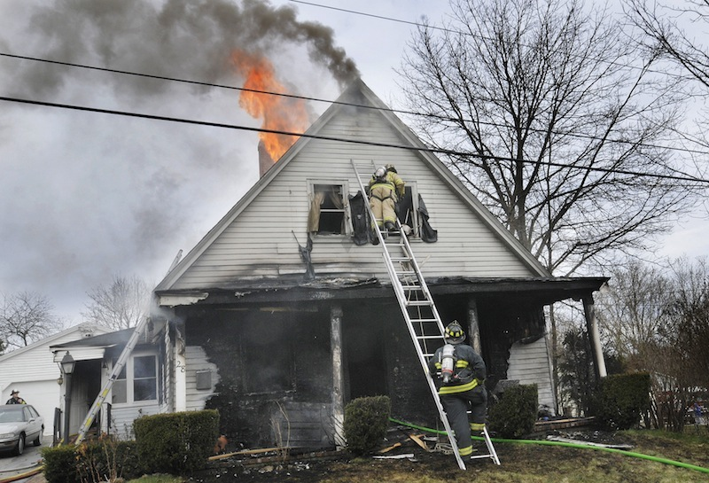 Firefighters battles the fire at 28 Raymond St. in Biddeford on Saturday morning March 31, 2012.