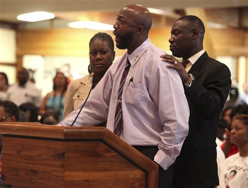 Tracy Martin, center, speaks at the Sanford City Commission meeting with Trayvon's mother, Sybrina Fulton, left, and the family lawyer, Benjamin Crump at the Sanford Civic Center in Sanford Fla., Monday.