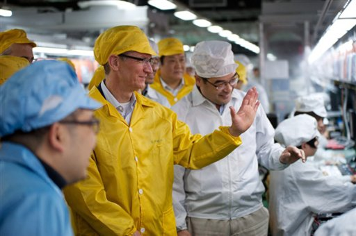 Apple CEO Tim Cook, center, visits the iPhone production line on Wednesday at a newly built manufacturing facility in Foxconn Zhengzhou Technology Park that employs 120,000 people. A report released today by the Washington-based Fair Labor Association says Hon Hai Precision Industry Co., the Taiwanese company that runs Apple's factories in mainland China, has committed to reducing weekly work time to the legal Chinese maximum of 49 hours.