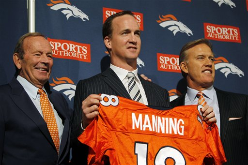 From left, Denver Broncos owner Pat Bowlen, newly-signed quarterback Peyton Manning and executive vice president of football operations John Elway pose for photos during a news conference at the team's headquarters in Englewood, Colo., today.