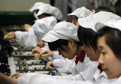 In this 2010 photo, staff members work on the production line at the Foxconn complex in Shenzhen, in southern China.