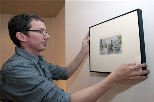 Director of DAAP Galleries at the University of Cincinnati, Aaron Cowan hangs a piece of art by art forger Mark A. Landis.