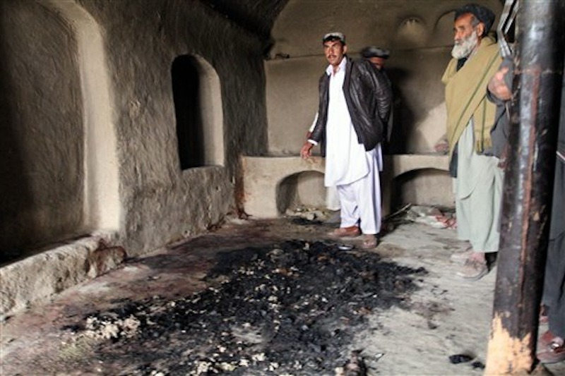 In this Sunday, March 11, 2012 photo, men stand next to blood stains and charred remains inside a home where witnesses say Afghans were slaughtered by a U.S. soldier in southern Afghanistan. (AP Photo/Allauddin Khan)