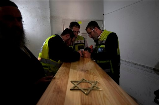 Israeli burial officials prepare the coffins of Toulouse shooting victims for their funeral, after they arrived to Israel, at a morgue in Jerusalem today.