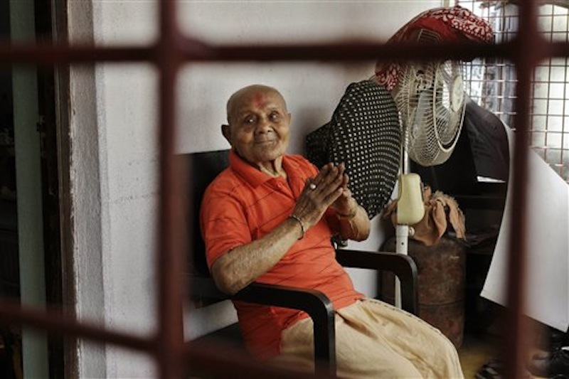 Indian body builder Manohar Aich sits in the balcony in Kolkata, India on Sunday, March 18, 2012. Aich, a former Mr. Universe who has just turned 100 said Sunday, that happiness and a life without tensions are the key to his longevity. Aich, who is 4 foot 11 inches (150 centimeters) tall, overcame many hurdles, including grinding poverty and a stint in prison, to achieve body building glory. (AP Photo/Bikas Das)