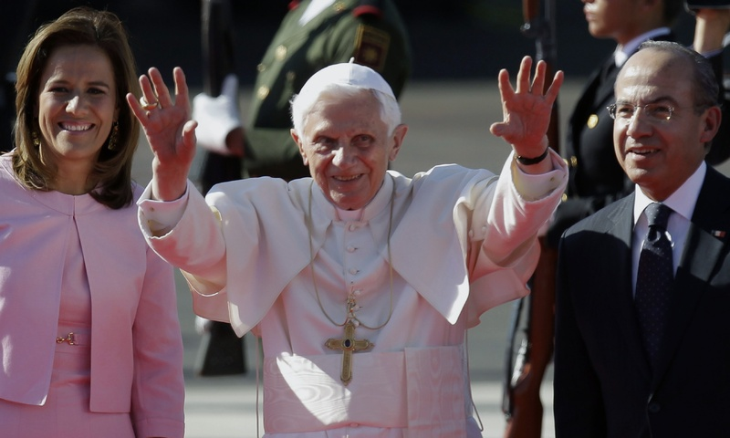 Pope Benedict XVI, accompanied by Mexico's President Felipe Calderon, right, and his wife Margarita Zavala, waves as he arrives at the airport in Silao, Mexico on Friday.