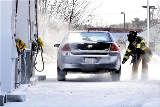 Skowhegan Fire Department Capt. Rick Caldwell wears protective gear while using an air hose to blow off fire suppressant powder that covered vehicles, customers and the ground at the Irving Circle K store. At least one person was sent to the hospital and several were examined.