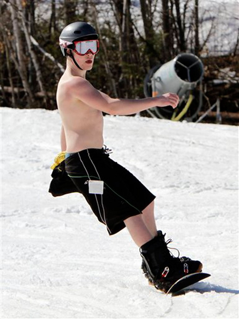 Ben Landry, 15, from Prince Edward Island, Canada, enjoys the warm sun while snowboarding in unusual weather for this time of year at Sunday River in Newry, Maine, on Wednesday, March 21, 2012. (AP Photo/Pat Wellenbach)