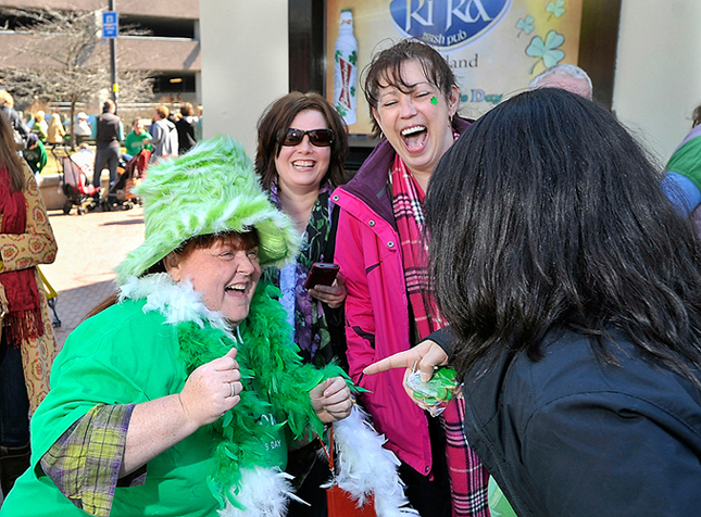 Liz Meserve of Portland entertains her friends with her outfit as she enjoys her first full day of celebrating St. Patrick's Day on Saturday, March 17, 2012. She is standing in line at Ri Ra's after having her first corned beef and cabbage breakfast at Brian Boru's.