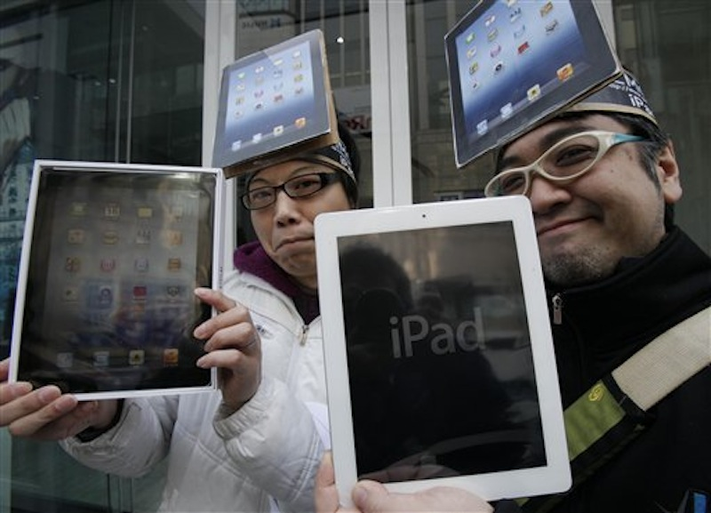 Japanese Ryota Musha, 41, right, and Hisanori Kogure, 31, show off new iPad tablet computers they purchased in Tokyo today. Sales of the third version of Apple's iPad began Friday morning in the U.S. and across the world. (AP Photo/Koji Sasahara)