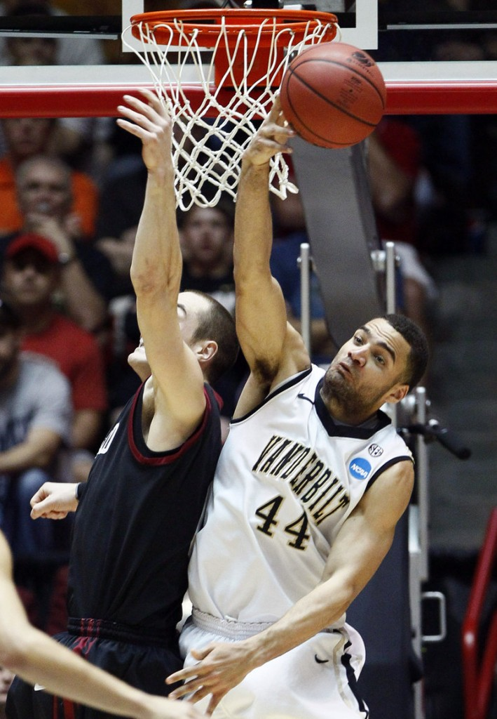 Jeffery Taylor of Vanderbilt knocks away a shot by Laurent Rivard, who finished with 20 points Thursday for Harvard. Vanderbilt advanced to meet Wisconsin after a 79-70 victory.