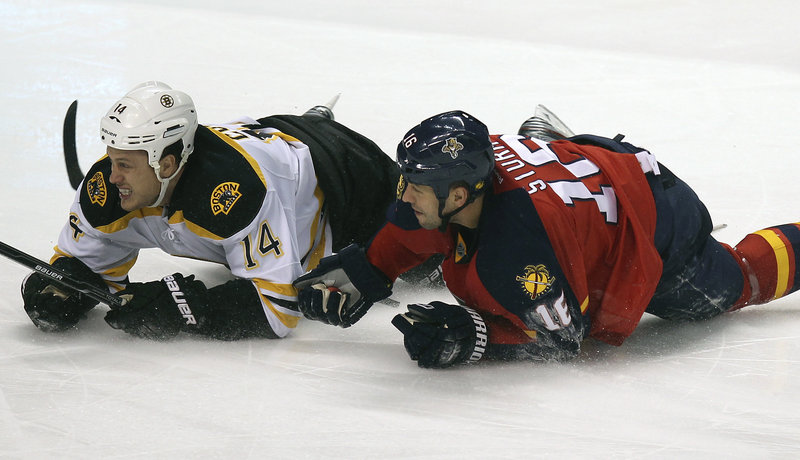 Joe Corvo of the Bruins, left, and the Panthers' Marco Sturm look for the puck after tumbling to the ice during the second period of their game Thursday night. Florida won, 6-2.