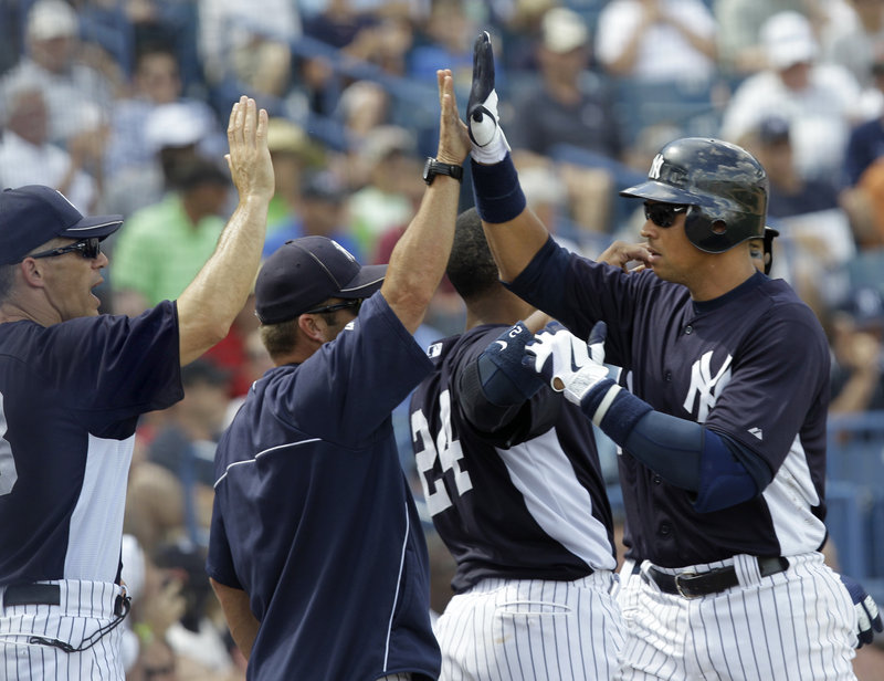 Alex Rodriguez, right, is greeted by Yankees Manager Joe Girardi, left, and hitting coach Kevin Long after hitting a two-run homer Friday against the Washington Nationals. The Yankees won 4-3 in 10 innings at Tampa, Fla.