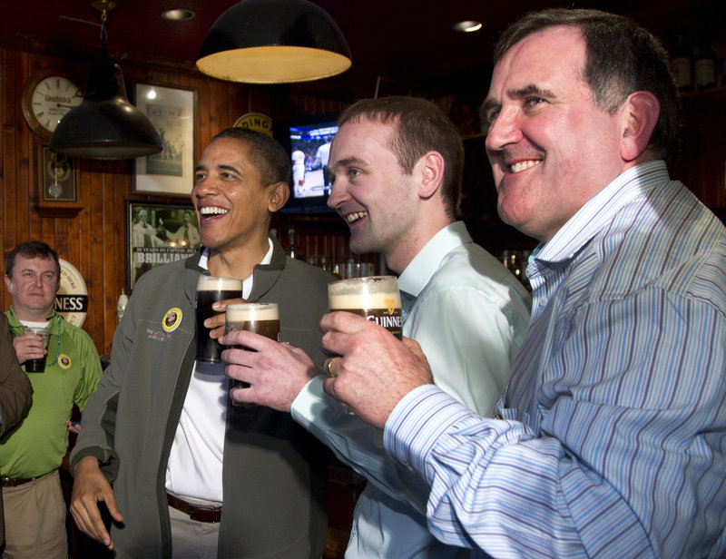 President Obama drinks a Guinness with his cousin Henry Healy, center, and the owner of the pub in Moneygall, Ireland, Ollie Hayes.