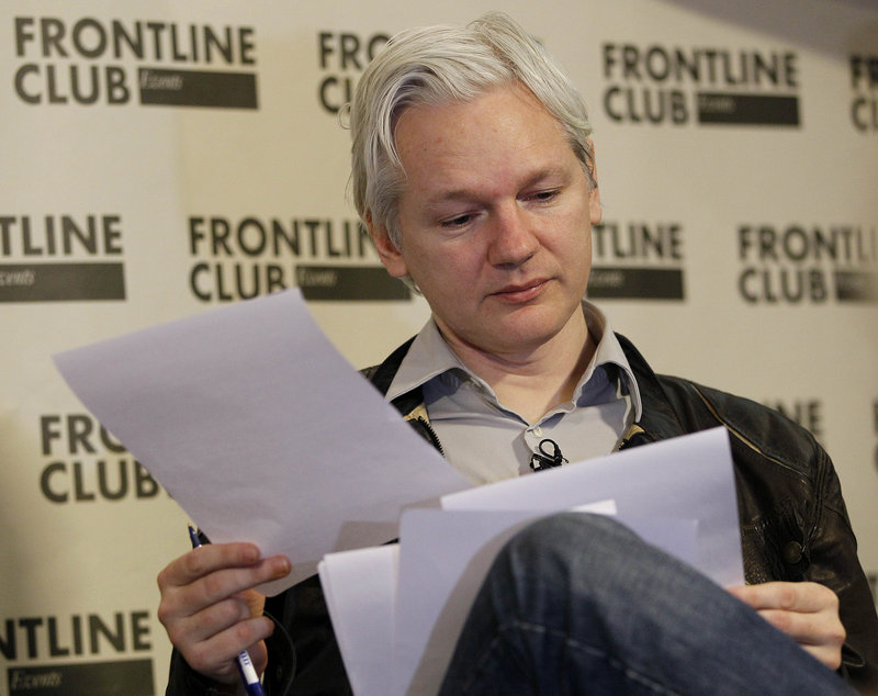Julian Assange looks at paperwork during a news conference in London in February. The WikiLeaks founder would be a long shot for a Senate seat in Australia.